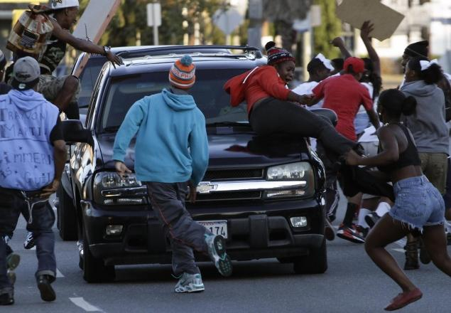Protestors jumping on vehicles. -Reuters